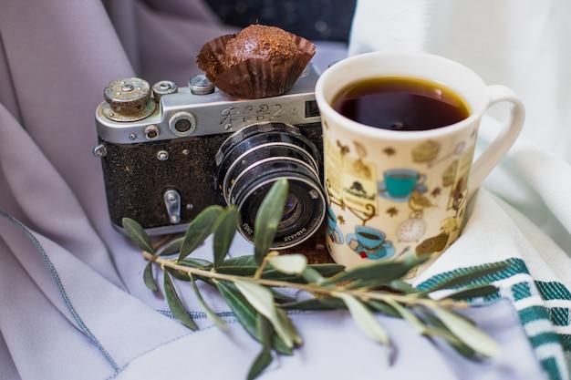 Una tazza di tè con una pralina al cioccolato e una macchina fotografica. Foto Gratuite