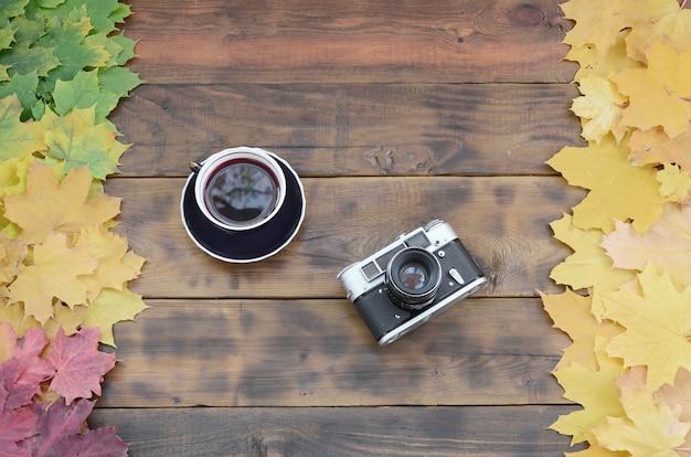 Una tazza di tè e una vecchia macchina fotografica in un insieme di foglie d'autunno cadute ingiallimento Foto Premium