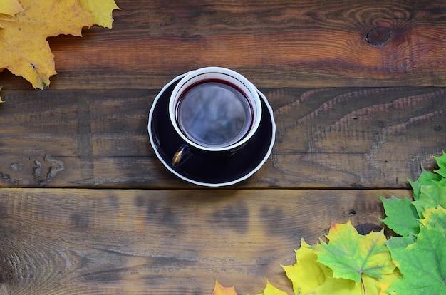 Una tazza di tè in un insieme di ingiallimento foglie cadute d'autunno su uno sfondo Foto Premium