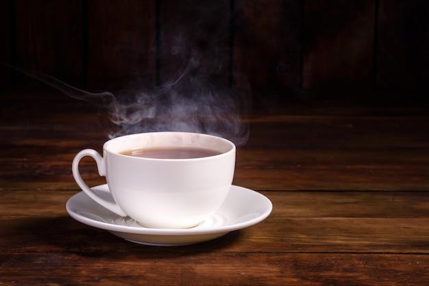 Una tazza di tè nero appena preparato, vapore che fuoriesce, luce calda e morbida Foto Premium