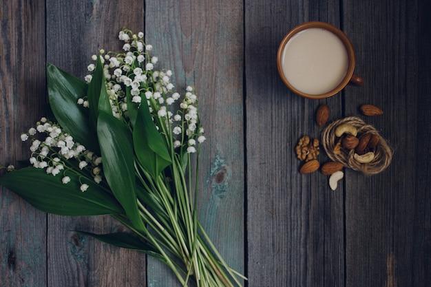 Una tazza di tè, noci, bouquet di gigli su un fondo di legno Foto Premium
