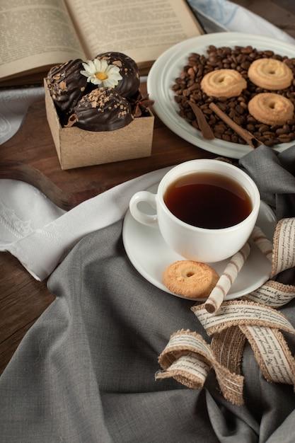 Una tazza di tè, praline e biscotti Foto Gratuite
