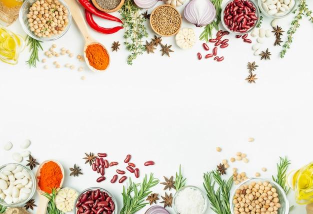 Una varietà di spezie ed erbe su un tavolo luminoso. tavolo da cucina vista dall'alto ingredienti per cucinare. menu tabella tavolo. Foto Premium