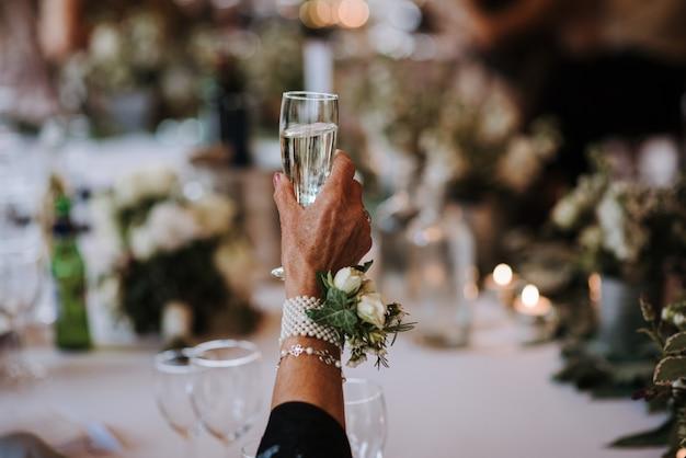 Una vecchia femmina in possesso di un bicchiere di champagne con un fiore appuntato su un accessorio sulla sua mano Foto Gratuite