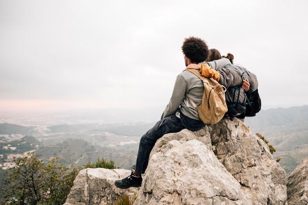 Una viandante di due maschi che si siede sopra la roccia sopra la montagna che esamina vista scenica Foto Gratuite