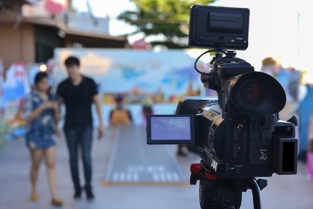 Una videocamera che utilizza lo streaming video in diretta con attori che camminano davanti Foto Premium