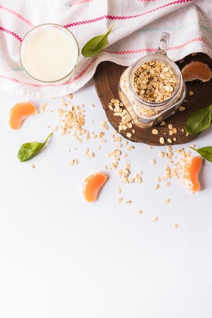 Una visione elevata del latte; foglie di basilico; avena; fette d'arancia e tovagliolo su sfondo bianco Foto Gratuite