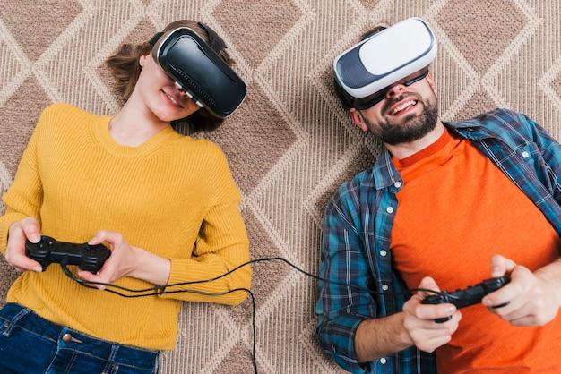 Una visione elevata della giovane coppia sdraiata sul tappeto indossando la fotocamera di realtà virtuale giocando al videogioco Foto Gratuite