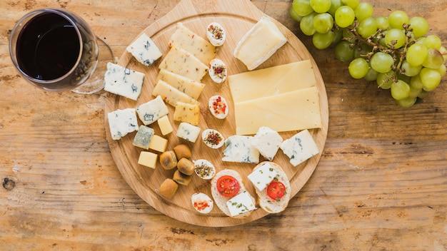 Una vista aerea del bicchiere di vino rosso con blocchi di formaggio e pomodori sullo scrittorio di legno Foto Gratuite