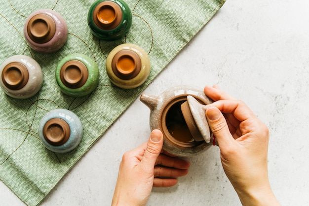Una vista aerea del coperchio della teiera di apertura della mano con tazze da tè colorate sul tovagliolo verde Foto Gratuite