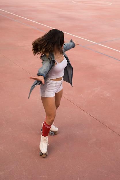 Una vista aerea del pattinatore femminile che oscilla sulla corte Foto Gratuite
