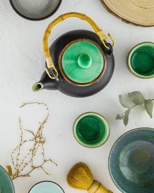 Una vista aerea del set da tè cinese tradizionale con pennello su sfondo bianco strutturato Foto Gratuite