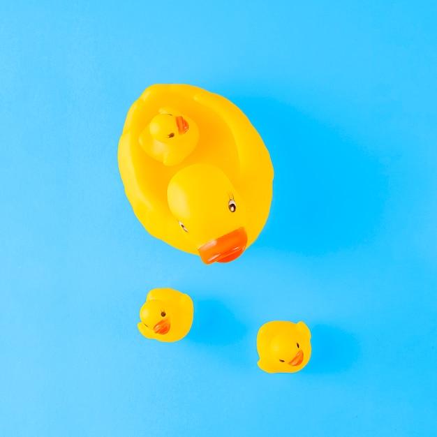 Una vista aerea dell'anatra di gomma gialla sveglia con gli anatroccoli contro priorità bassa blu Foto Gratuite