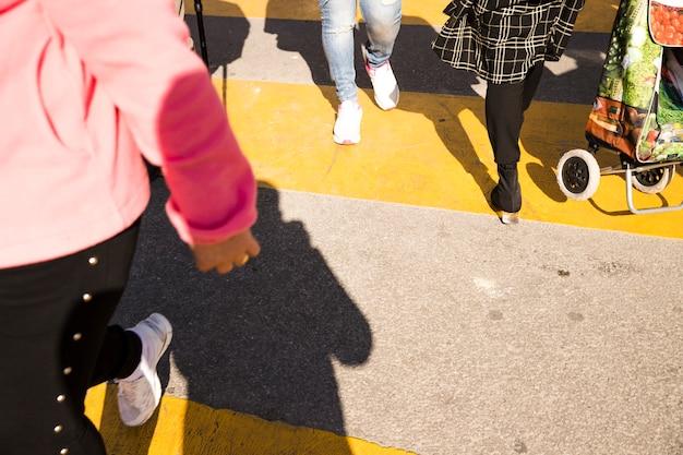 Una vista aerea della gente che attraversa sull'asfalto giallo del crosswalk Foto Gratuite