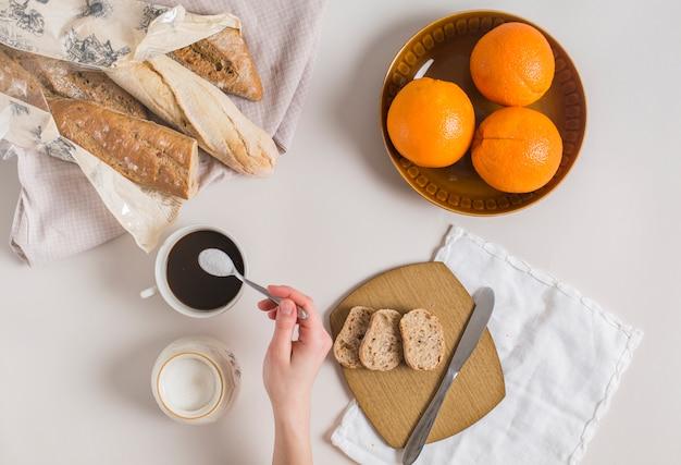 Una vista aerea della mano di una donna aggiungendo latte in polvere nella tazza di tè con pane e arance su sfondo bianco Foto Gratuite
