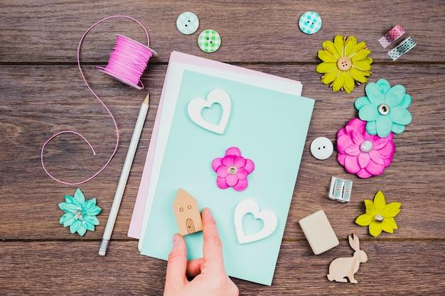 Una vista aerea della mano umana che fa biglietto di auguri con fiori e blocco di casa in legno sulla scrivania Foto Gratuite
