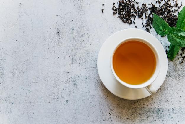 Una vista aerea della tazza di tisana alla menta su sfondo concreto Foto Gratuite