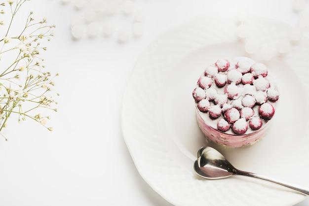 Una vista aerea della torta deliziosa con il cucchiaio di forma del cuore sul piatto bianco contro il contesto bianco Foto Gratuite
