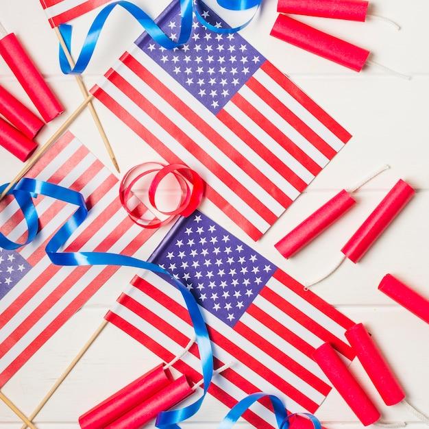 Una vista aerea delle bandiere americane con nastri e petardo sullo scrittorio bianco Foto Gratuite