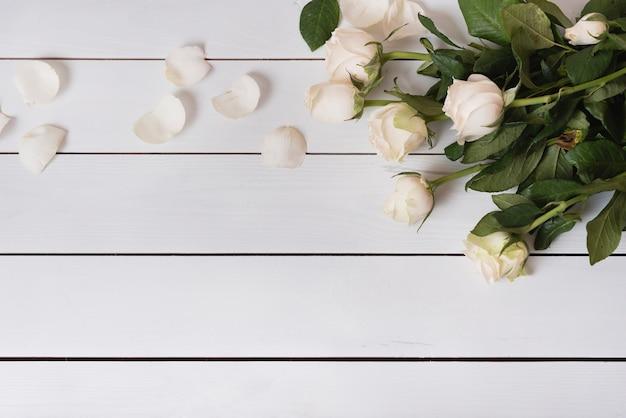 Una vista aerea delle belle rose bianche fresche sulla tavola di legno Foto Gratuite