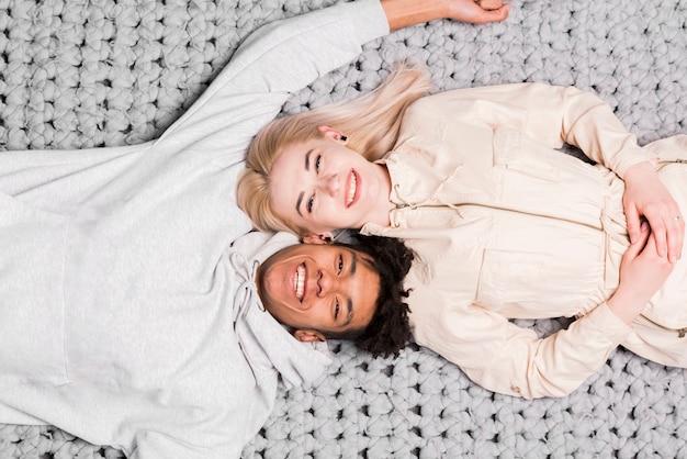 Una vista aerea delle giovani coppie interrazziali sorridenti che si trovano sulla coperta grigia Foto Gratuite