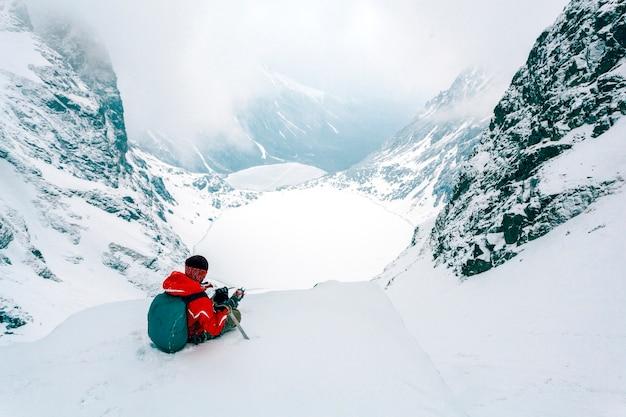 Una vista aerea dello sciatore che si siede sulla cima della montagna nevosa delle alpi Foto Gratuite