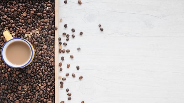 Una vista aerea di chicchi di caffè tostato e tazza di caffè Foto Gratuite
