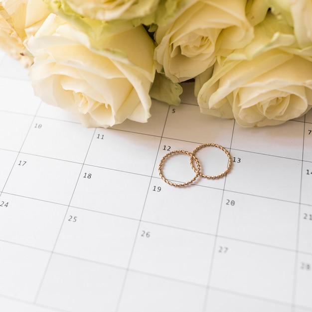 Una vista aerea di fedi nuziali e rose sul calendario Foto Gratuite