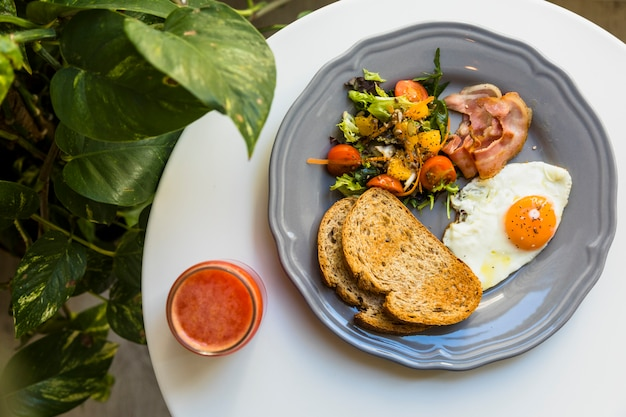 Una vista aerea di frullato e colazione sul piatto in ceramica sul tavolo bianco vicino alla pianta di apezio epipremnum Foto Gratuite