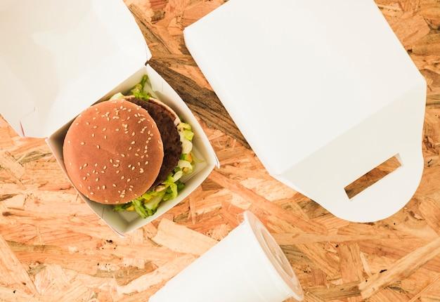 Una vista aerea di hamburger nel pacchetto sullo sfondo in legno Foto Gratuite