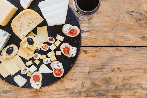 Una vista aerea di mini panini con formaggio e pomodori sullo scrittorio di legno Foto Gratuite