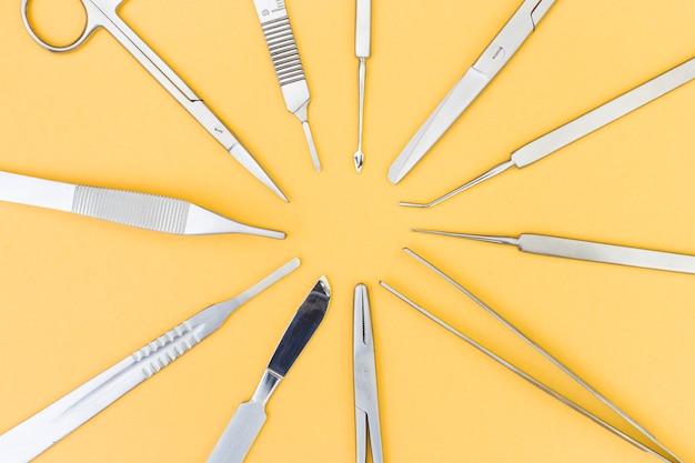Una vista aerea di strumenti per la chirurgia plastica su sfondo giallo Foto Gratuite