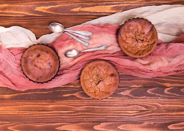 Una vista aerea di torte al cioccolato al forno con cucchiaio e vestiti sul contesto in legno Foto Gratuite