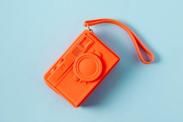 Una vista aerea di una borsa arancione a forma di telecamera su sfondo blu Foto Gratuite
