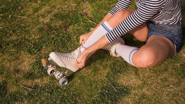 Una vista aerea di una donna che si siede sull'erba verde che lega pizzo sul pattino a rotelle Foto Gratuite