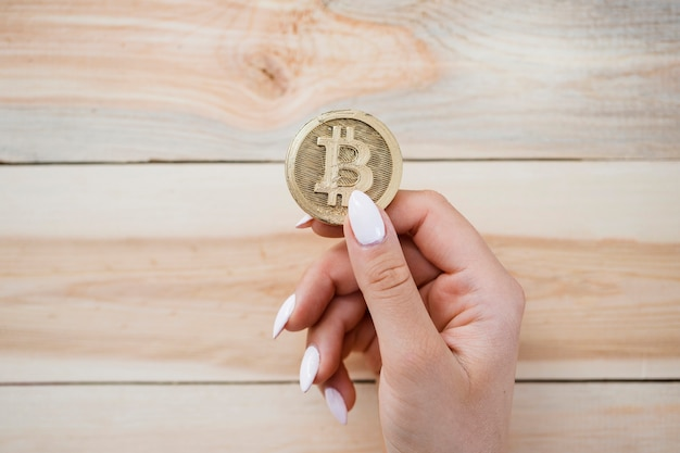 Una vista ambientale dei bitcoins della holding della mano della femmina contro priorità bassa di legno Foto Gratuite