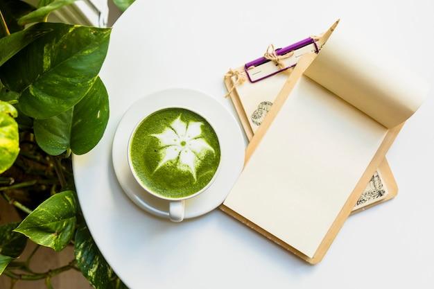 Una vista ambientale della tazza calda del latte del tè verde di matcha con i appunti sulla tabella bianca Foto Gratuite