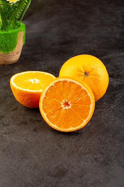 Una vista dall'alto arance fresche acide mature intere e affettate agrumato dolce tropicale giallo vitamina sulla scrivania scura Foto Gratuite