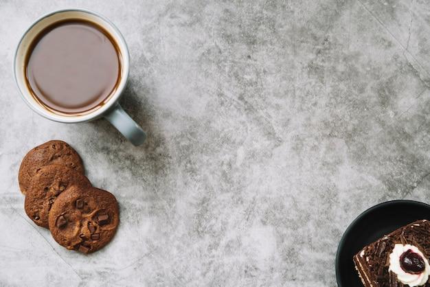 Una vista dall'alto dei cookie; torta e tazza di caffè su un vecchio fondale Foto Gratuite
