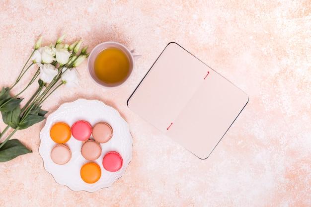 Una vista dall'alto dei fiori eustoma; tazza di tè verde; amaretti sul piatto bianco e blocco note vuoto su fondo rustico Foto Gratuite