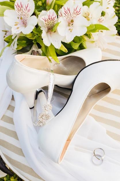 Una vista dall'alto dei fiori; tacchi alti; corona; sciarpa e fedi nuziali sul tavolo Foto Gratuite