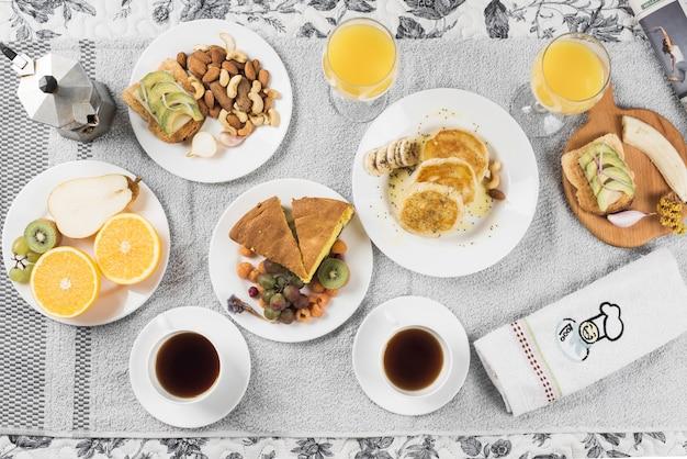 Una vista dall'alto dei frutti; panini; pancake; torta sui piatti sopra il tovagliolo Foto Gratuite