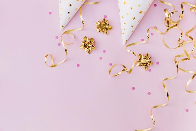 Una vista dall'alto del cappello di carta bianca; cospargere; arco dorato e streamer su sfondo rosa Foto Gratuite