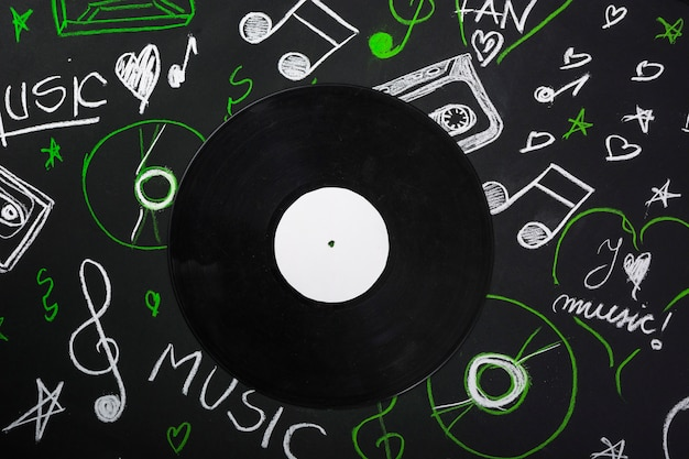 Una vista dall'alto del disco in vinile sulla lavagna con note musicali disegnate Foto Gratuite