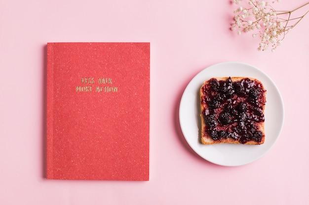 Una vista dall'alto del libro rosso; brindisi con marmellata di bacche e fiori del respiro del bambino su sfondo rosa Foto Gratuite