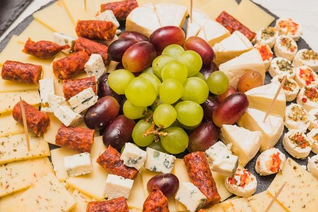 Una vista dall'alto del piatto di formaggi; uva e salsicce affumicate Foto Gratuite
