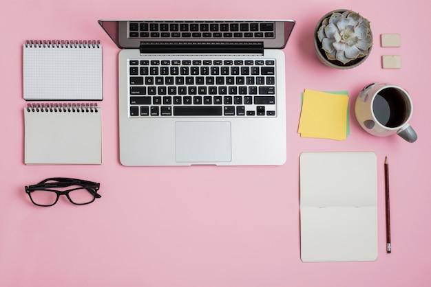 Una vista dall'alto del portatile; bloc notes; occhiali; note adesive; pianta di cactus e tazza di tè su sfondo rosa Foto Gratuite