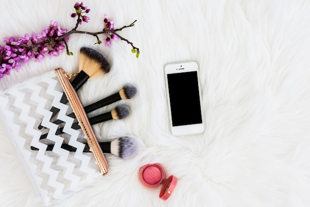 Una vista dall'alto del ramoscello viola con pennelli per il trucco; telefono cellulare e cipria compatta rosa su pelo bianco Foto Gratuite