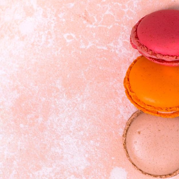 Una vista dall'alto del rosa; maccheroni arancioni e marroni sulla priorità bassa del grunge Foto Gratuite