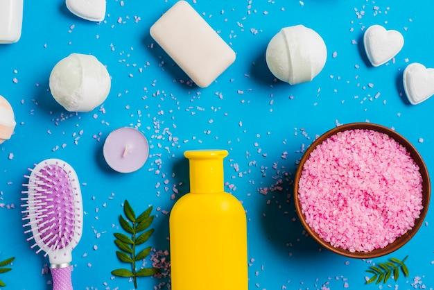 Una vista dall'alto del sale himalayano; sapone e spazzola per i capelli su sfondo blu Foto Gratuite